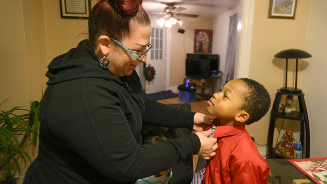Mary Jo Newtown helps grandson Deveon Timmons, 7, with his tie in the dining room of their Rochester apartment Friday, Nov. 25, 2016.