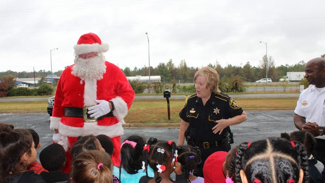 """Santa Claus (Sgt. Buck Wilkins of the Bossier Parish Sheriff's Office) and Sgt. Tina Fruge greeted children from Bossier Head Start on Monday as local law enforcement's holiday initiative, """"Operation Santa Claus,"""" kicked off. The community is asked to help by donating monetarily or with unwrapped Christmas gifts."""
