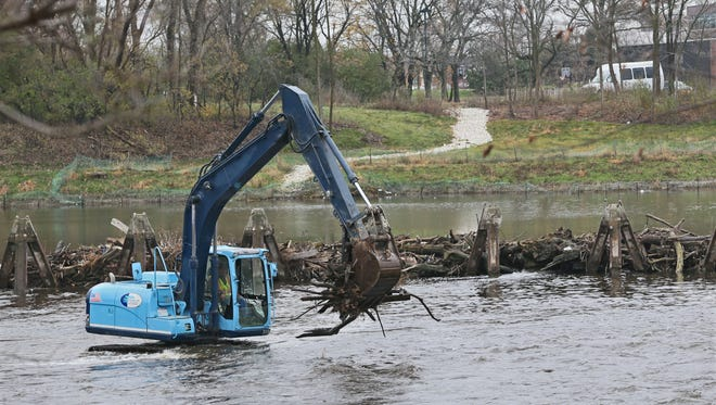 An excavator driver with D.F. Tomasini removes tree trunks, branches and other debris from ice barriers upstream of the Estabrook Park dam on the Milwaukee River on Monday.