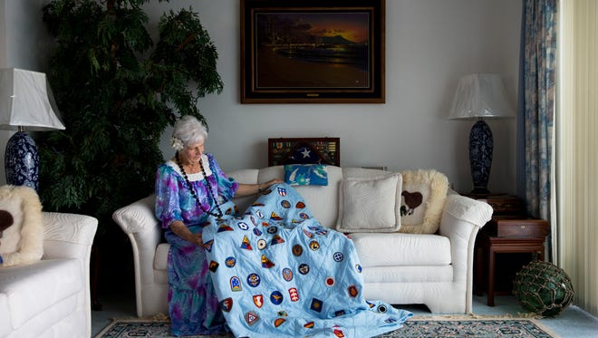 Leilani Roberts displays her patch quilt in her East Naples home on Sunday, Dec. 4, 2016. Roberts, who was five years old at the time, watched the attack on Pearl Harbor from her home near Waikiki on the island of Oahu in Hawaii. She collected 156 uniform patches from men who stayed with her family throughout WWII, which she later used to make a commemorative quilt.