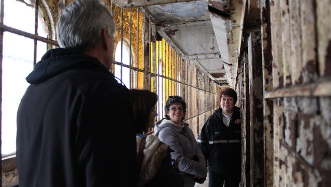 (From left to right) Rick Foote, Christ Foote and Kelly Foote, all of Medina, listen to Diana Riggleman, volunteer coordinator with the Mansfield Reformatory Preservation Society,  in one of the cell blocks at the Ohio State Reformatory during a Christmas tour Sunday, Dec. 4, 2016.