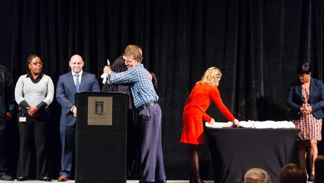 Scott hugs Judge Robert Helfrich after the judge handed him his certificate during Monday's drug court graduation.