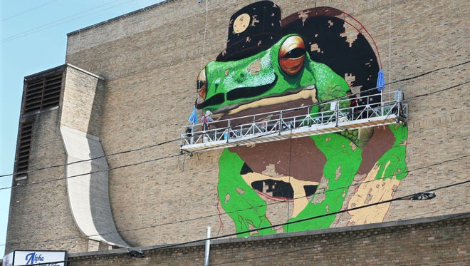 The mural of a giant frog with a mustache is part of a larger project, the Black Cat Alley, which will bring other street artists, local and internationally known, to Milwaukee. The alley  runs between E. Ivanhoe Place and E. Kenilworth Place, behind the Oriental Theater on N. Farwell Ave.
