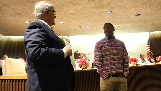 """Mayor Tim Theaker presents a proclamation to Mansfield Senior High School athlete Brian Benson at the Mansfield City Council meeting Tuesday. Theaker proclaimed the date to be """"Brian Benson Day"""" in Mansfield in honor of  Benson's academic, athletic and community achievements."""