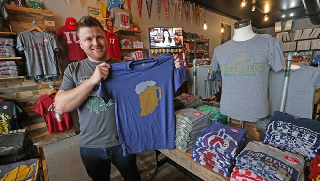 """Brian Kelly, Hayes & Taylor Quality Clothing Co.'s owner,  holds up his most popular selling shirt, """"Drink Indiana,"""" at his Broad Ripple store, The Shop,  920 Broad Ripple Ave. Business boomed on Black Friday and Small Business Saturday for the clothing store."""