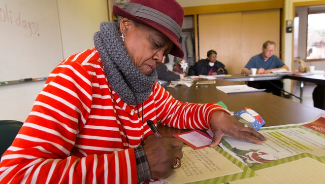 Helen Dobson, 69, checks over a letter from Santa to a child on Thursday at the Washington Park Senior Center in Milwaukee.