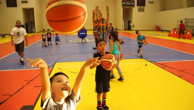 Young basketball athletes take aim at a youth hoop during a Guam Elite Basketball Academy camp.