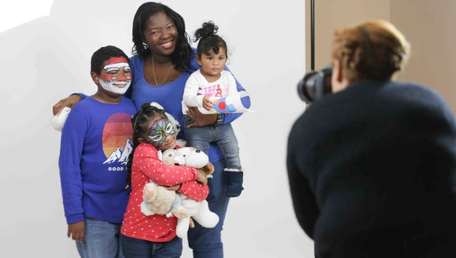 Left to right, Fantino, Celeste, mother Diana, and Lidaly Flores are photographed by Photographer Faith Blackwell during the Help-Portrait Indianapolis event, held at the Athenaeum, Sunday, Dec. 11, 2016. Those with a need of any kind were invited to enjoy free hair, makeup, portraits, and food donated by Indianapolis professionals.