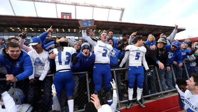 Sayreville quarterback Jayson DeMild holds up the sectional trophy for fans after the team defeated Middletown North in North 2 Group IV sectional football championship at Rutgers University's High Point Solutions Stadium.