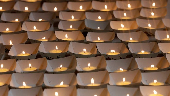 Candles are lined up before being passed out.