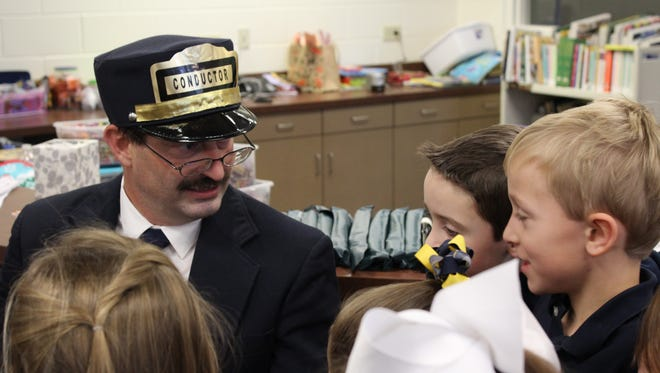 """The Polar Express Conductor (aka Steve Carter) recently took time out of his very busy schedule to meet with students at John Paul II Catholic School.  The conductor read his most favorite book to the students, """"The Polar Express"""".   Students Brady Steward and Rylan Hagan had some interesting questions for the Conductor."""