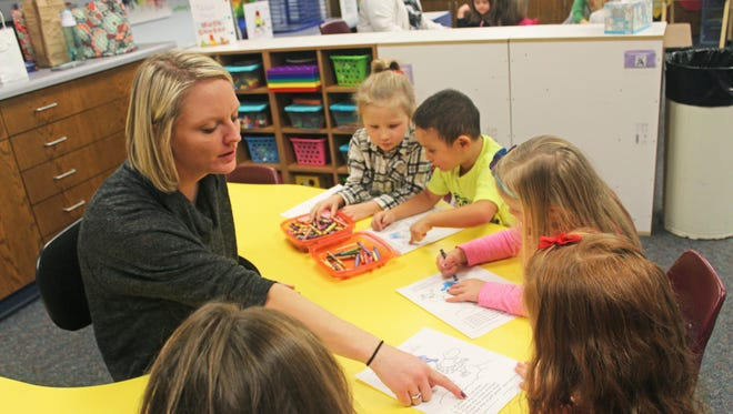 From left to right: Shimek Elementary preschool teacher Sara Kayser works on coloring sheets that promote motor skills and following directions with Analise Bailey, Jacob Fountain and other students on Dec. 21, 2016.