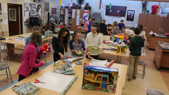 Pathfinder School students wrap gifts they raised money for to give to a local family in need.
