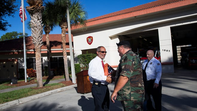 US Army SSG Wilfredo Vasquez, left, shakes hands with his friend Frank Kerr after receiving an American flag during a surprise ceremony at the North Collier Fire Station #45 in Naples, Fla., on Sunday, Dec. 25, 2016. For the past four years, the North Collier Fire Veterans-Armed Forces Council has honored a service member with a dedicated American flag and certificate on Christmas Day.