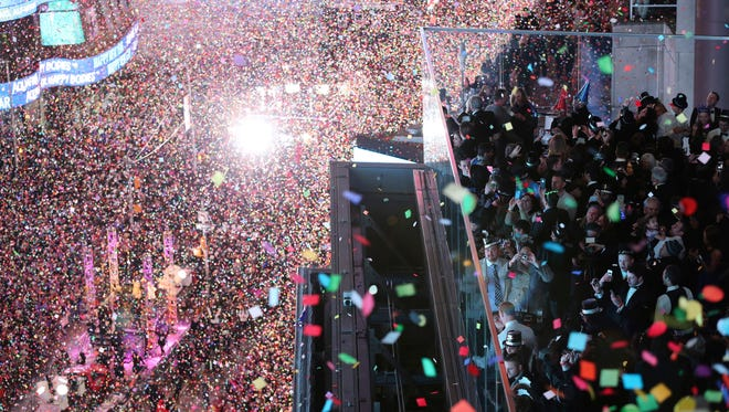 In this Jan. 1, 2016, file photo, revelers celebrate as confetti flies over New York's Times Square after the clock strikes midnight during the New Year's Eve celebration as seen from the Marriott Marquis hotel.