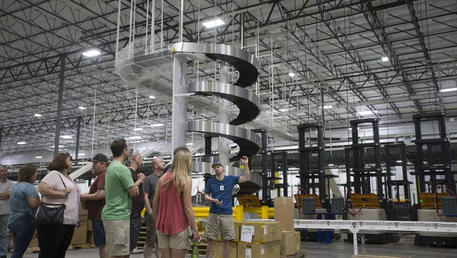 Sam Thompson shows off the warehouse at REI's Fulfillment Center on July 7, 2016, in Goodyear. The official opening was scheduled for July 11, 2016.
