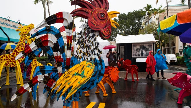 Two women browse Frederick Prescott's kinetic sculptures during the 21st annual Naples New YearÕs Art Fair on 5th Avenue South on Saturday, Jan. 7, 2016. Despite the inclement weather, festival goers came out to browse over 200 artist booths offering a wide range of original works from oils on canvas to hand-crafted jewelry and more.