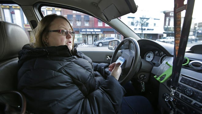 Tanya Ralston-Engle, who drives with Uber and Lyft, discusses the software applications as she splits the day before and after the Packers game on Jan. 8 in Appleton.