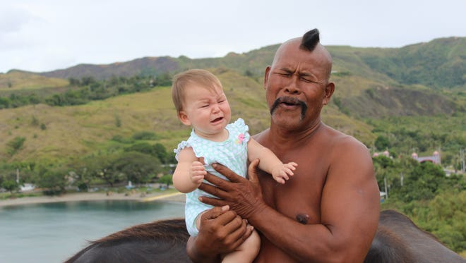 """Mel Reed shared this photo of her child Natalie as she is held by """"Big John"""" Tedtaotao."""