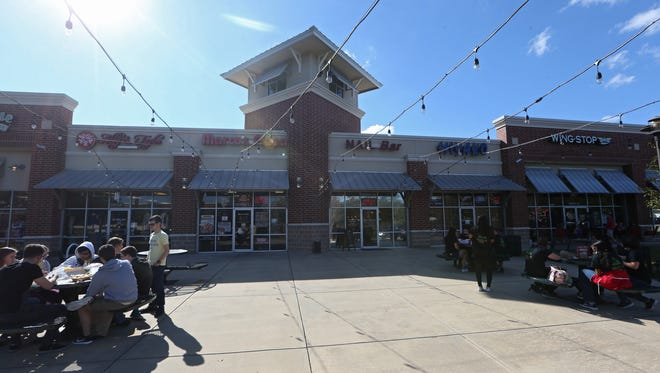 People shop and dine at Bannerman Crossing, the commercial heart of a four-precinct Trump enclave where the presidential elect garnered between 54 and 58 percent of votes cast.