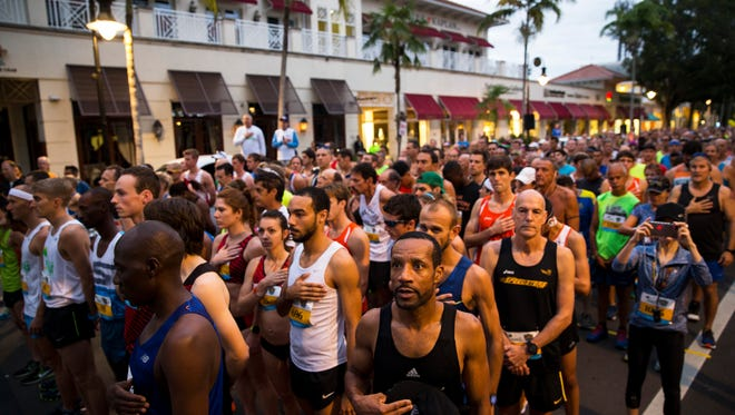 Runners listen to the playing of the National Anthem before the start of the Naples Daily News Half Marathon in downtown Naples on Sunday, Jan. 15, 2017. The USATF certified course began on 5th Avenue South and returned to Cambier Park, where refreshments and post race massages were available to runners.