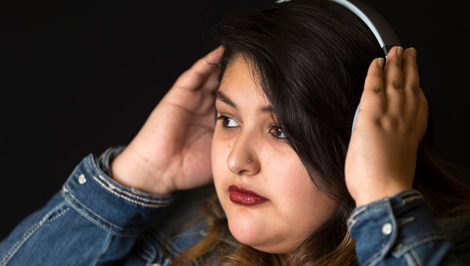 Part of the Kids in Crisis series about youth mental health, Reyna Saldana, a recent high school graduate, copes with a difficult past in foster care through literature and listening to music. Pictures taken at Ethel Everhard Library on Jan. 5, 2017, in Westfield.