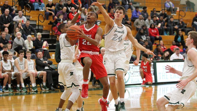 Pike's Elijah Pennington works against Zionsville's defense. Nathan Childress goes for the block.