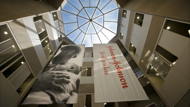 Banners hang in an atrium at the headquarters of Johnson & Johnson in New Brunswick. In a deal announced Thursday, the New Jersey drug titan is buying Swiss pharmaceutical Actelion in a $30 billion deal that will boost J&J's treatments for life-threatening high blood pressure conditions.