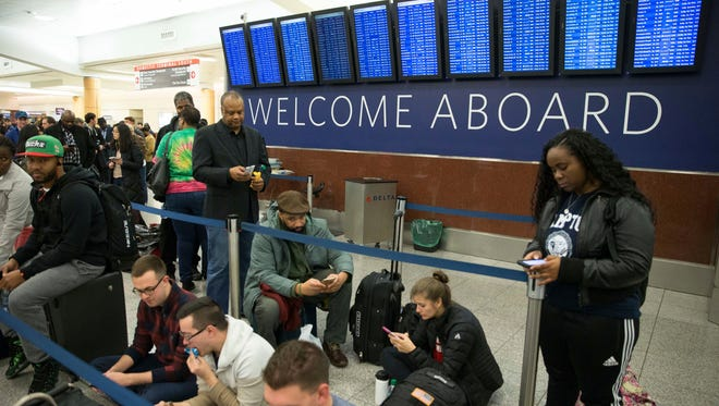 Delta passengers wait in line at Hartsfield-Jackson International Airport after Delta Air Lines grounded all domestic flights due to automation issues, Sunday, Jan. 29, 2017, in Atlanta. (AP Photo/Branden Camp)