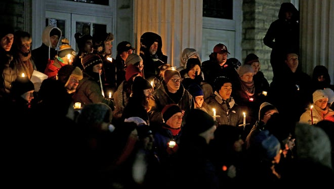Residents gather for a candlelight vigil Sunday on the steps of the Lawrence Memorial Chapel in Appleton to protest the immigration ban imposed by President Donald Trump.