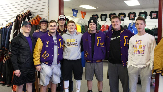 Noah Kabbaz (middle, in gray hoodie) poses for a photo with his Lexington football teammates at Johnny Johnson Sports in Ontario on Monday, Jan. 30, 2017. His teammates raised money to purchase a letterman jacket for Noah in honor of his father, who died earlier this month after a long illness.