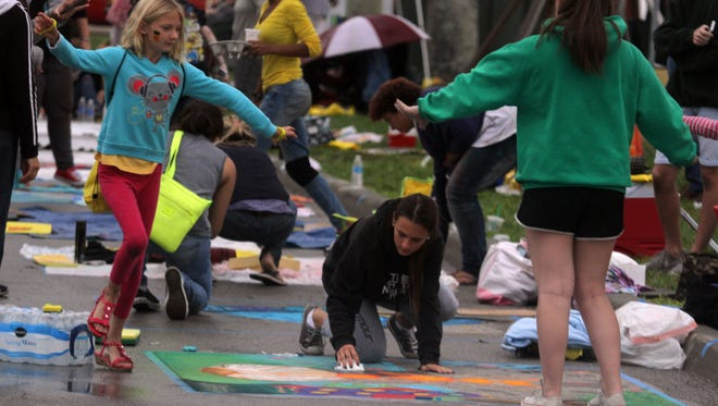 Students/artists work on chalk block art during a past ArtFest in downtown Fort Myers.