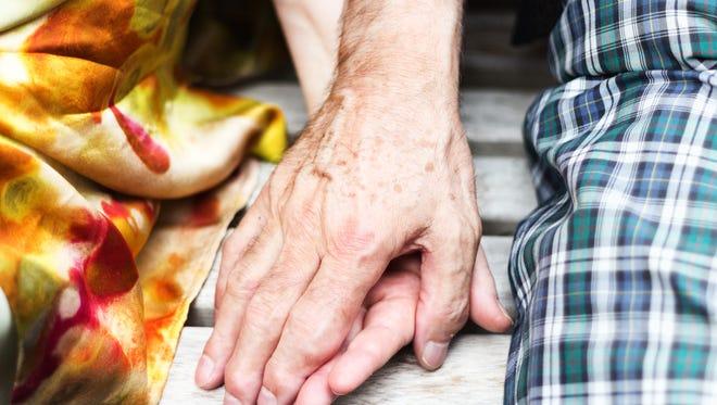 FILE -- senior couple holding hands