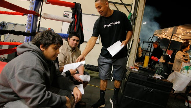 George Villa hands out paperwork to teens interested in free membership at his gym. Team Villa Boxing Gym held an open house fundraiser on Tuesday night.