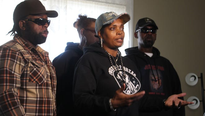 Activist Traci Fant, center, speaks about the death of Pat Charles Mackey while surrounded by his family Saturday.