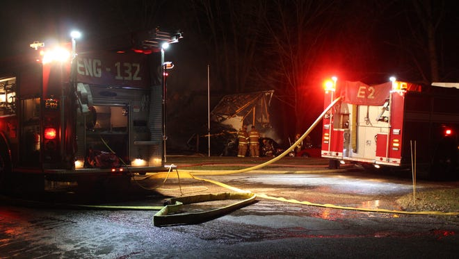 Firefighters work at the scene of a house fire on Walnut Drive South on Sunday. The house was a total loss.