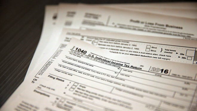 Tax forms sit on a desk at the start of the tax season rush, inside the offices of tax preparation firm Infinite Tax Solutions, in Boulder, Colo. Filing taxes early could speed your return and protect your identity.