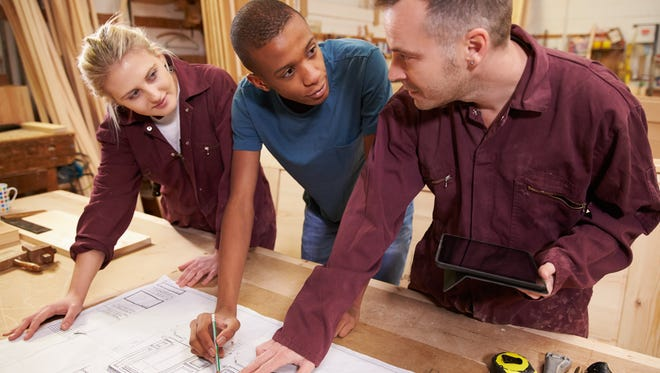 Carpenter with apprentices looking at plans.
