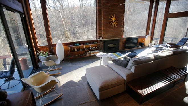 A general view of the living room featuring floor-to-celing windows. This 2,300 square foot home, pictured, Thursday, Feb. 2, 2017, in Wyoming, Ohio, was designed by architect Ben Dombar, and is among several modern homes found along Congress Run creek.