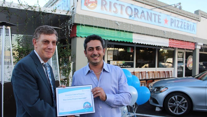 Dr. Allen Weiss, chief executive officer of the NCH Healthcare System, joins Gianluca Corso, right, to celebrate his restaurant earning Blue Zones Project recognition.