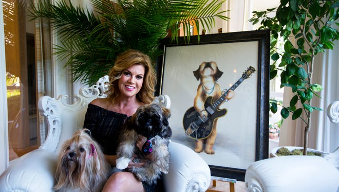 Amy Brazil poses for a portrait with her dogs Giada Gelato D'Amico and Leo Cannoli D'Amico at her home in Naples, Florida on Wednesday, Feb. 15, 2017. Brazil is well-known for her extravagant and realistic paintings of dogs, which often incorporate Swarovski crystals, various metals, and semi-precious gemstones.