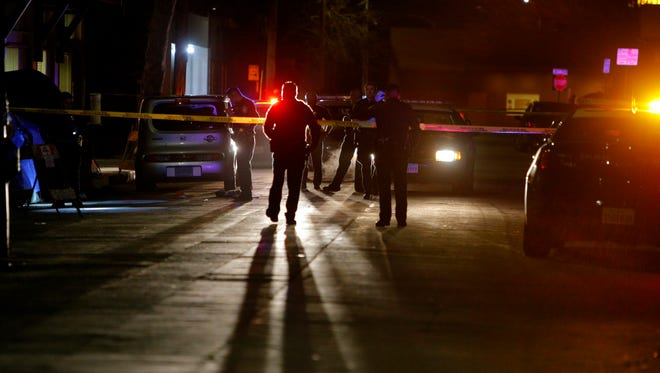 Police investigate the scene of a quadruple shooting in Chinatown on Wednesday night.