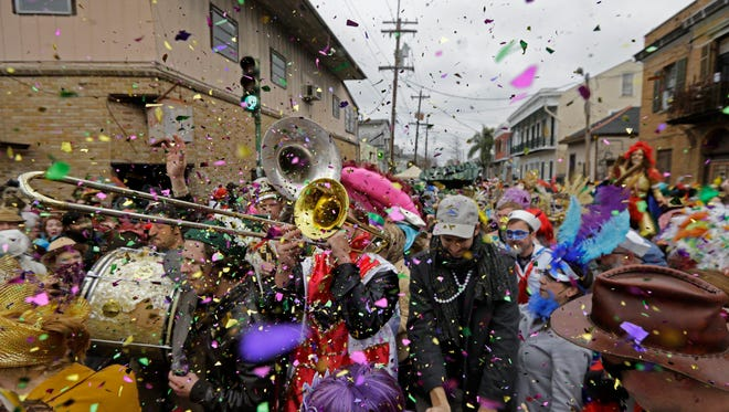 In this file photo, revelers play brass band music as they begin the march of the Society of Saint Anne Mardi Gras parade, on Mardi Gras in New Orleans.