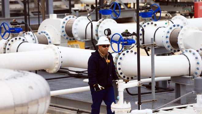 A docksman walks around pipes as crude is placed in the Theo T ship Wednesday, Dec. 31, 2015, at the NuStar Energy Dock 16 in Corpus Christi.