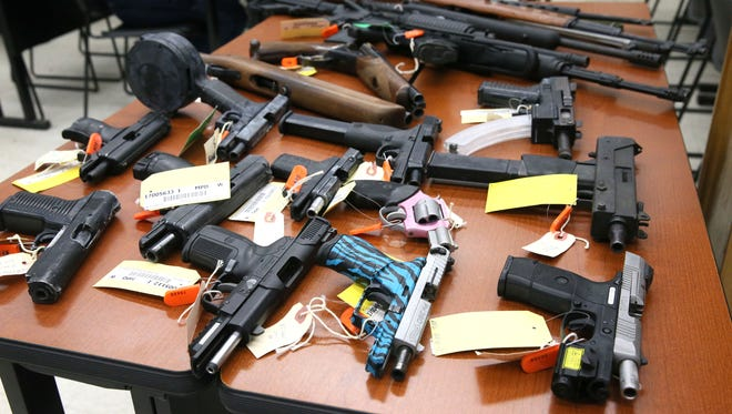An assortment of rifles, shotguns and handguns seized by Milwaukee police are on display Sunday at Milwaukee Mayor Tom Barrett's news conference at the  District 7 police station.