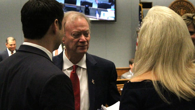 Louisiana Secretary of State Tom Schedler speaks with aides following the House and Government Affairs Committee meeting Monday.