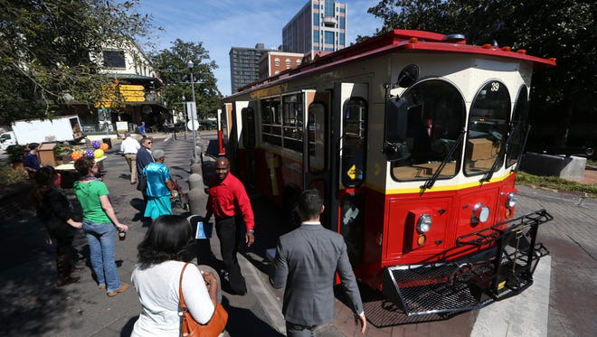 """Passengers board the """"T"""",  a free trolley system that will run on weekdays and into the night on the weekends with routes between downtown and the adjacent neighborhoods, that began service on Monday, Feb. 20, 2017."""