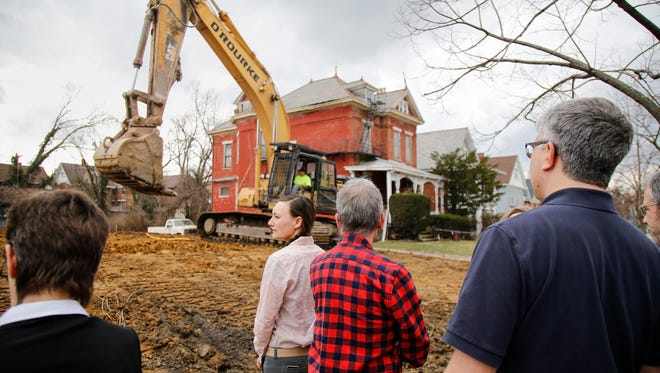 Jocelyn Welch, a East Walnut Hills resident, watches as work crews smooth out land that was slated to become an employee parking lot for UC Health, Thursday, Feb. 23, 2017, in the 1300 block of Myrtle Street in East Walnut Hills. UC Health on Wednesday scrubbed plans to expand an employee parking lot on a residential block of East Walnut Hills after neighbors fought back by seeking a city zoning change that would block parking lots from the area for good.