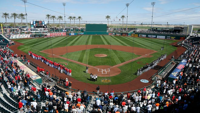 Fans rise for the signing of the National Anthem before the first inning of the MLB Spring Training game between the San Francisco Giants and the Cincinnati Reds at Goodyear Ballpark in Goodyear, Ariz., on Sunday, Feb. 26, 2017.