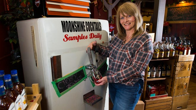 Co-owner Lisa Reissmann pours a sample of cherry moonshine at The Shinery in Neenah. Reissmann and her husband, Troy, plan to open a moonshine shop in Cedarburg in late April.